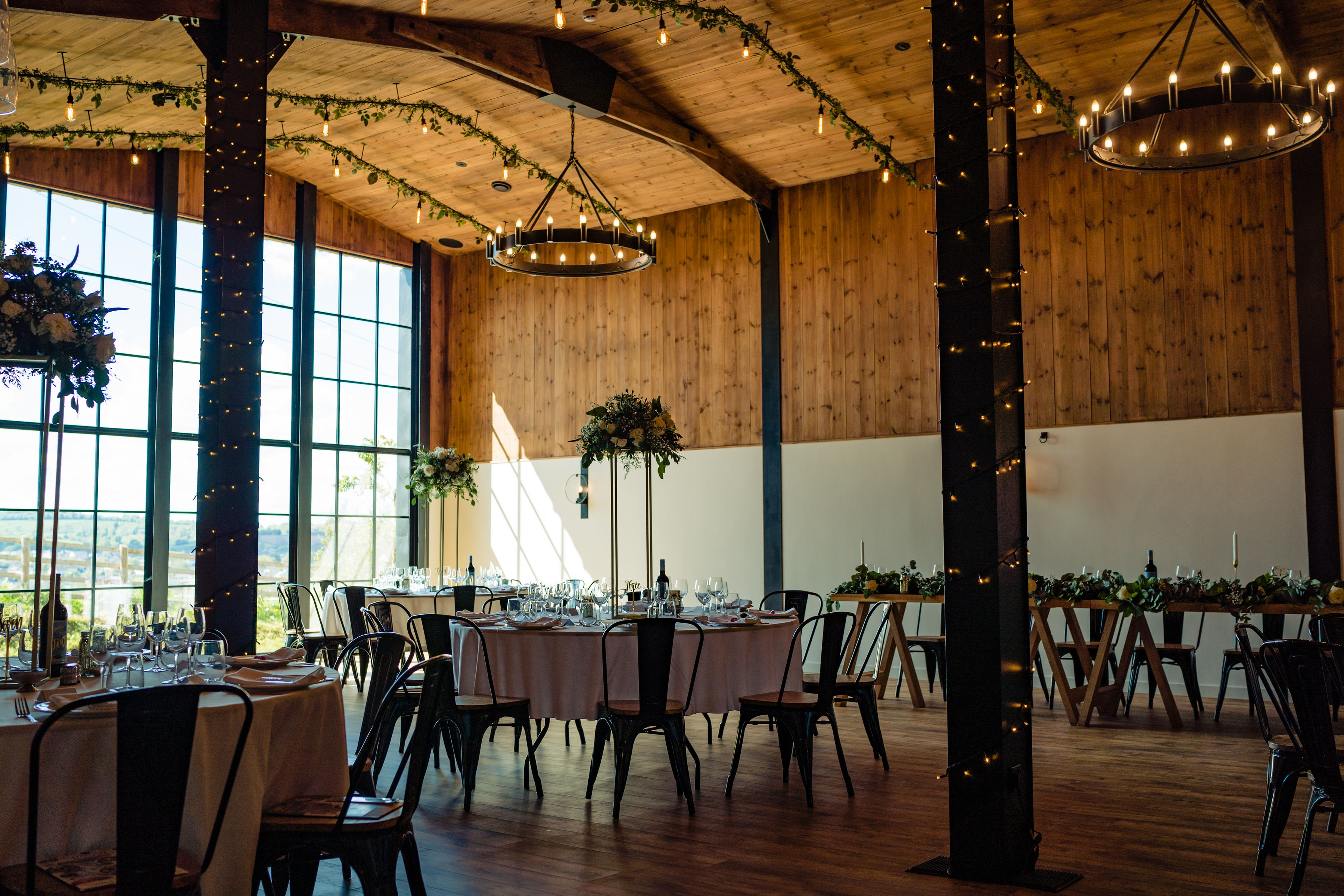 The Stable Barn set up for a Wedding Breakfast with light pouring through the large glass window