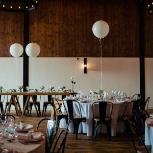 Black and White photo of The Stable Barn Dressed for a Wedding Breakfast  with oversized white balloons