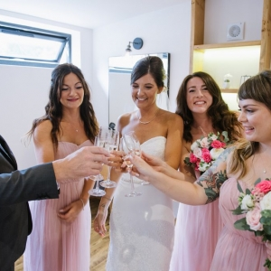 Bride, her maids and her father raise a toast