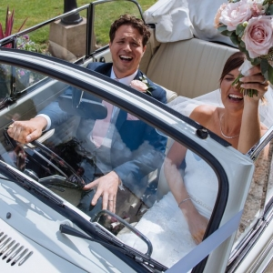 Bride and Groom with smiles in the wedding car
