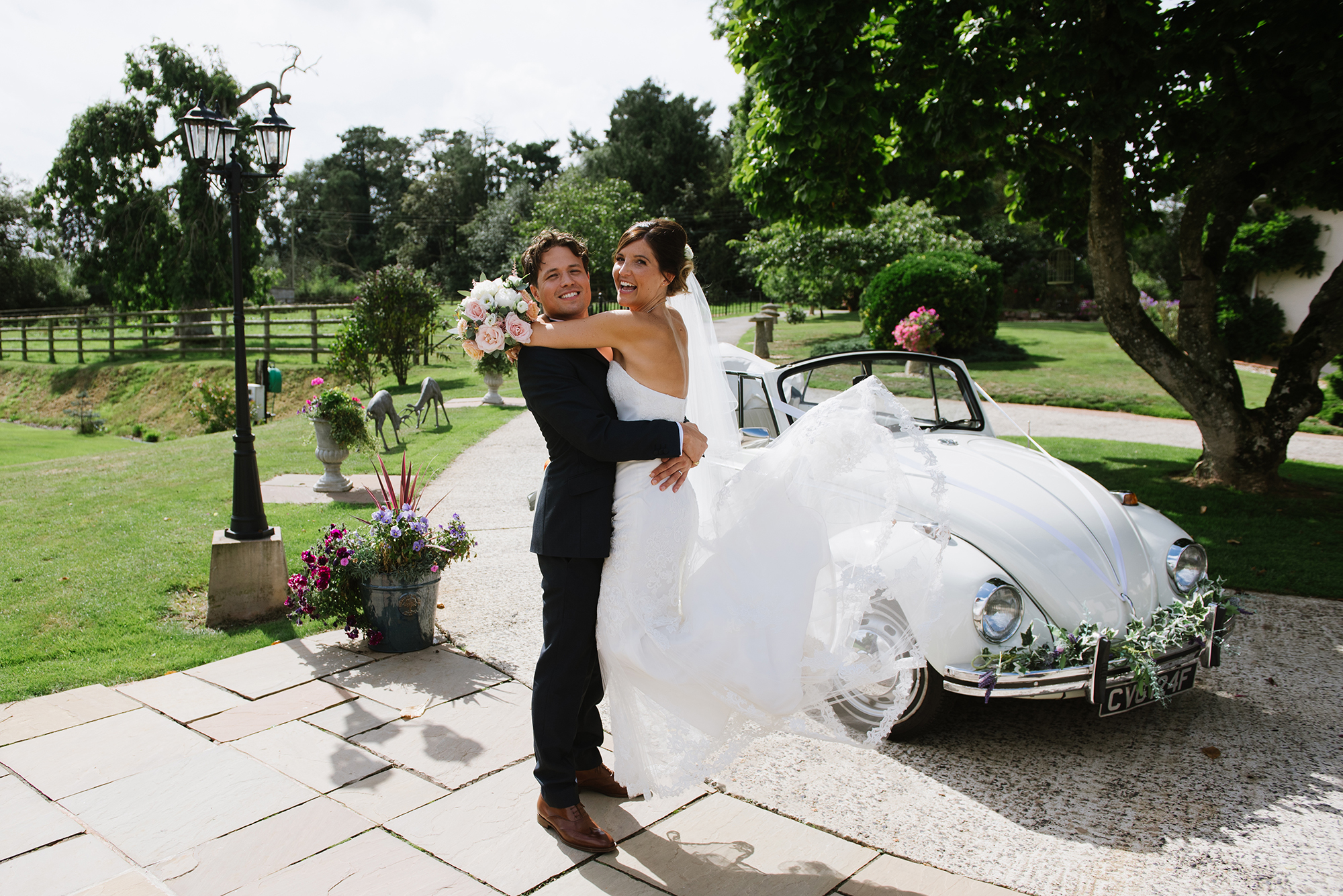 Bride and groom smile and embrace by VW wedding car