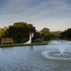 Bride & groom embrace by the fountain at Upton Barn