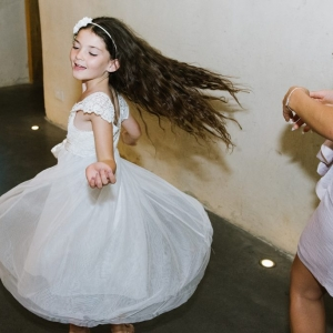 Bridesmaid spins and dances at a wedding in the Cider Barm