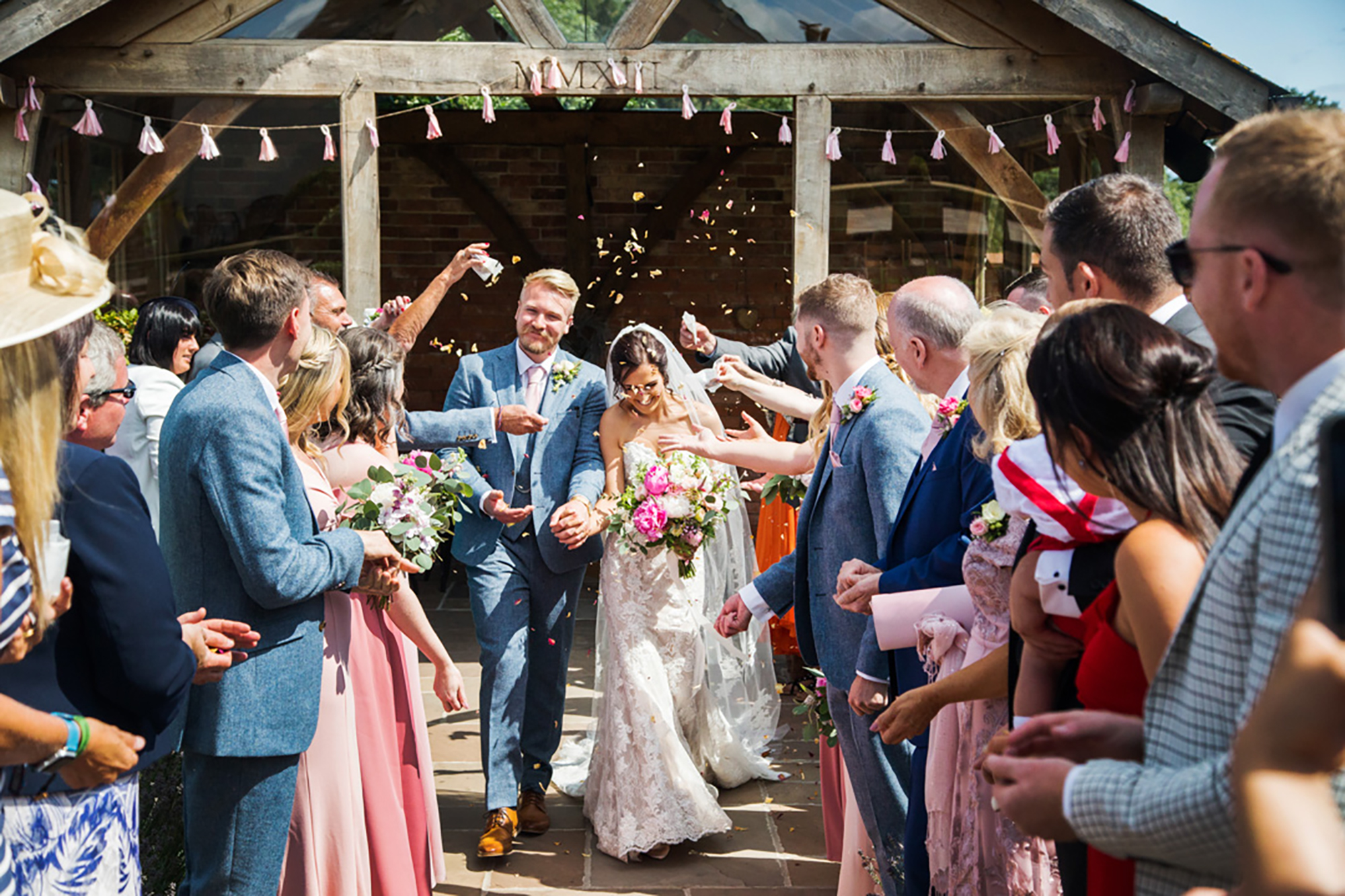 Bride and Groom are sprinkled with confetti by guests as they leave the Arbour at Upton Barn
