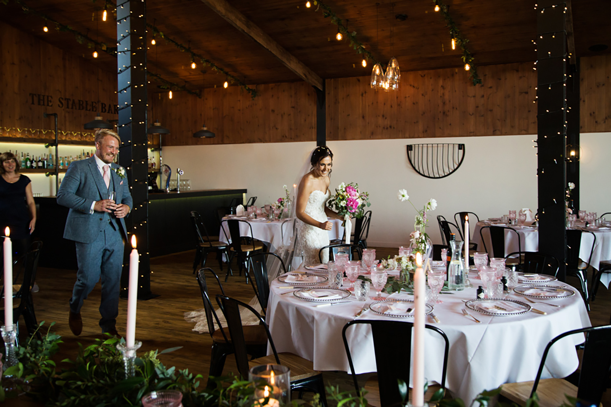 Bride and Groom walk past Wedding Breakfast tables in The Stable Barn at Upton