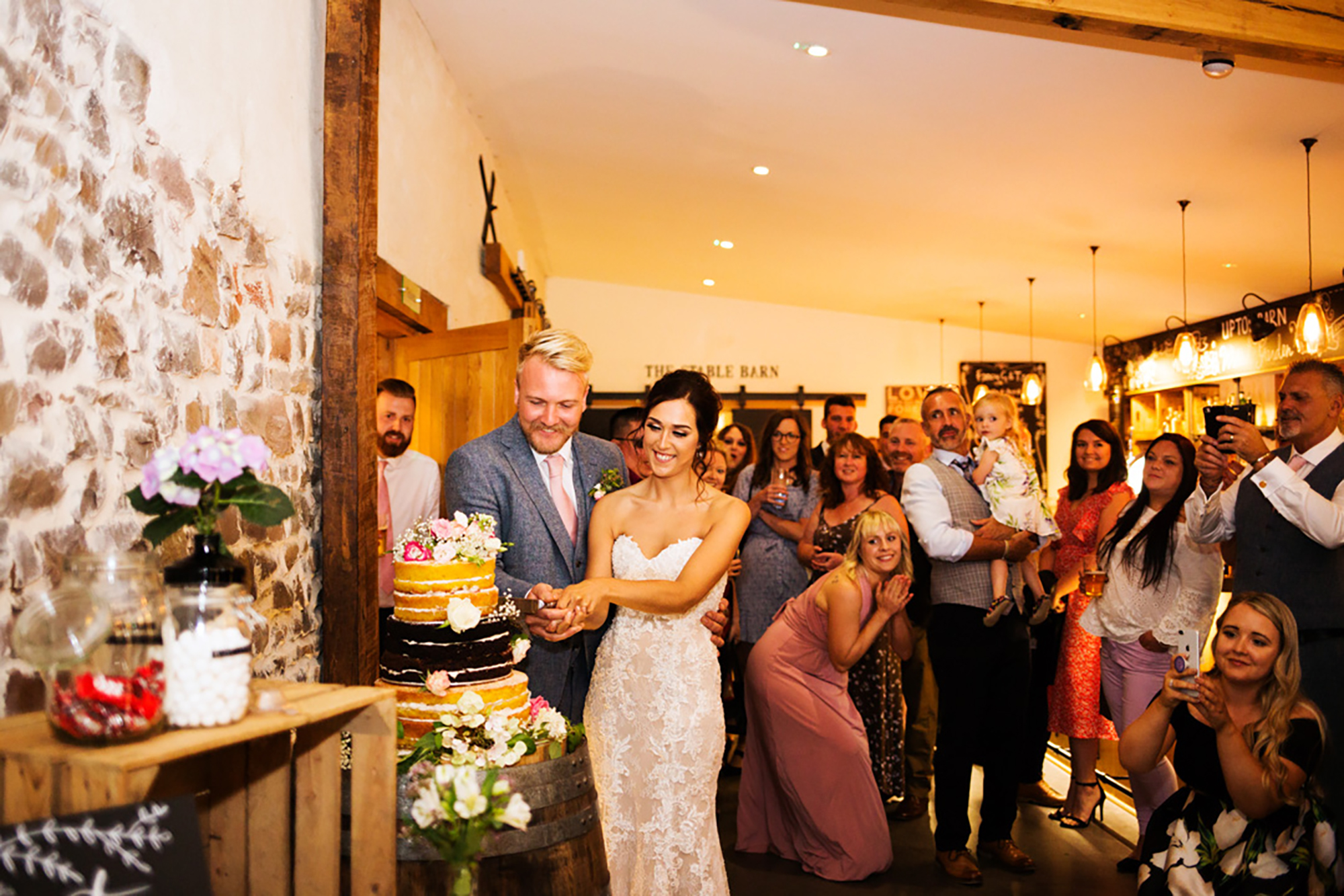 Bride and Groom cut wedding cake infront of their guests in the Press Bar