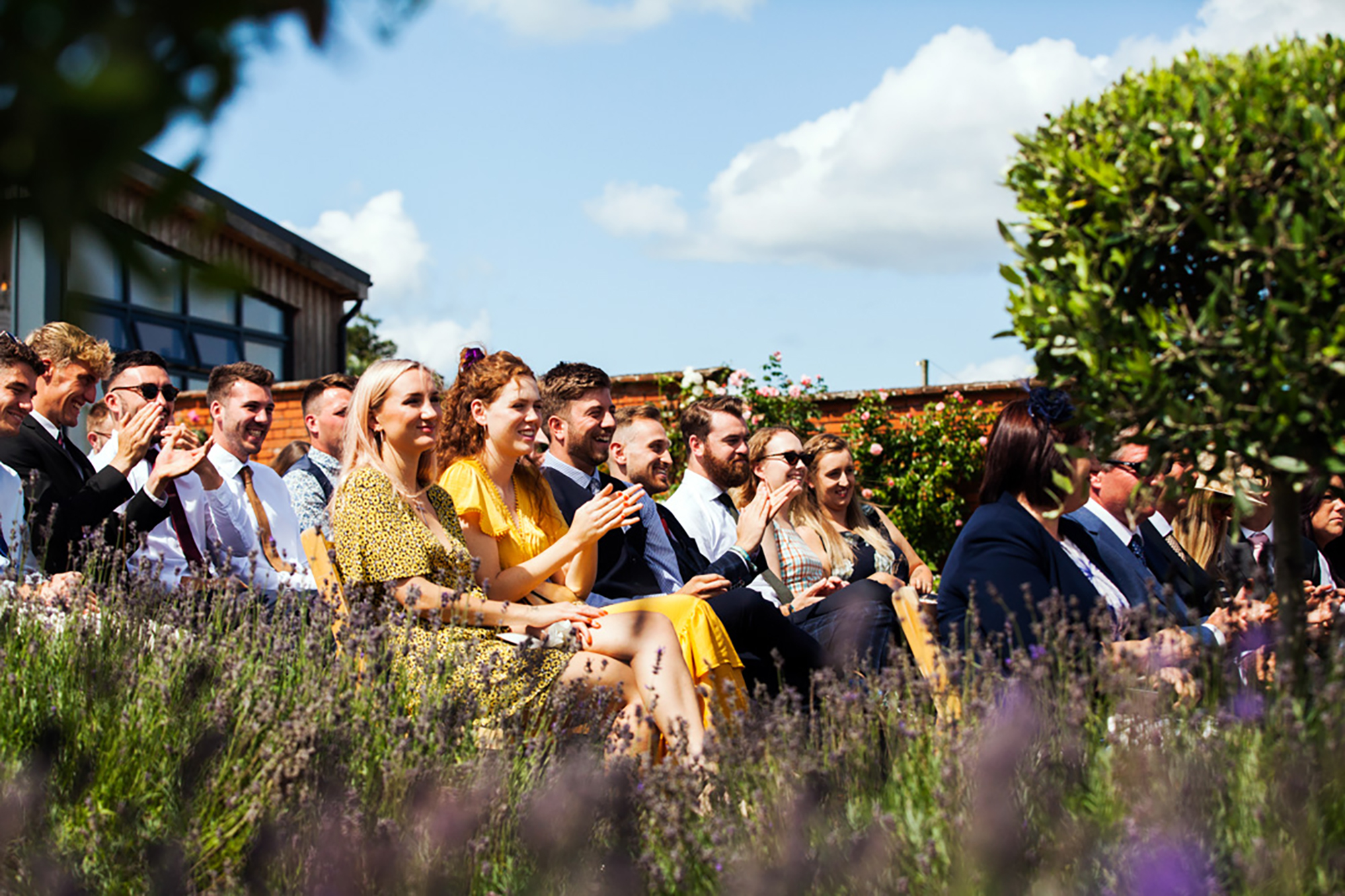 Seated guests in the Walled Garden clap to congratulate the bride and groom