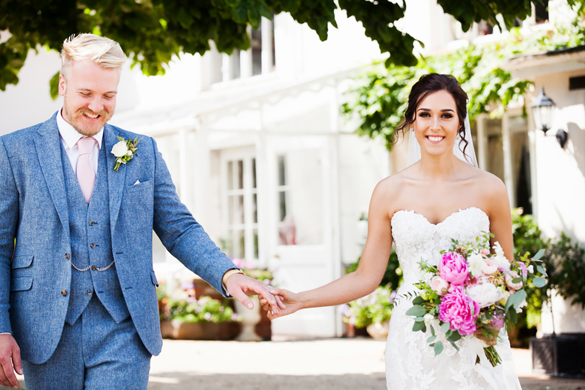 Bride and Groom hold hands in front of the house at Upton Barn