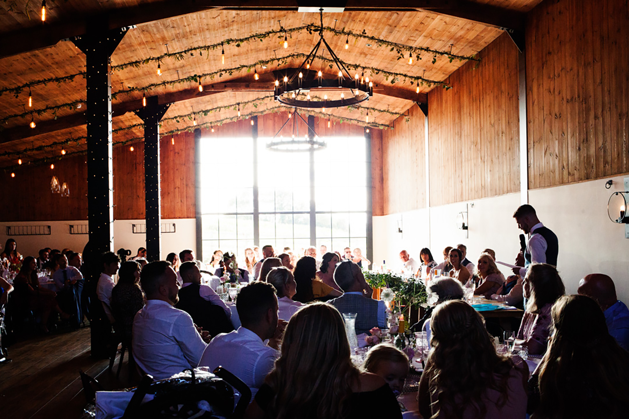 Best man delivers speech from top table in The Stable Barn as seated wedding guest look on