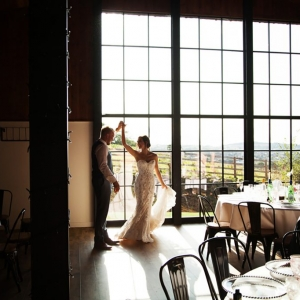 Bride and Groom dance in the light of the Stable Barn Window at Upton