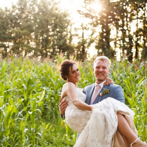 Groom holds his Bride up in his arms in a field of green corn