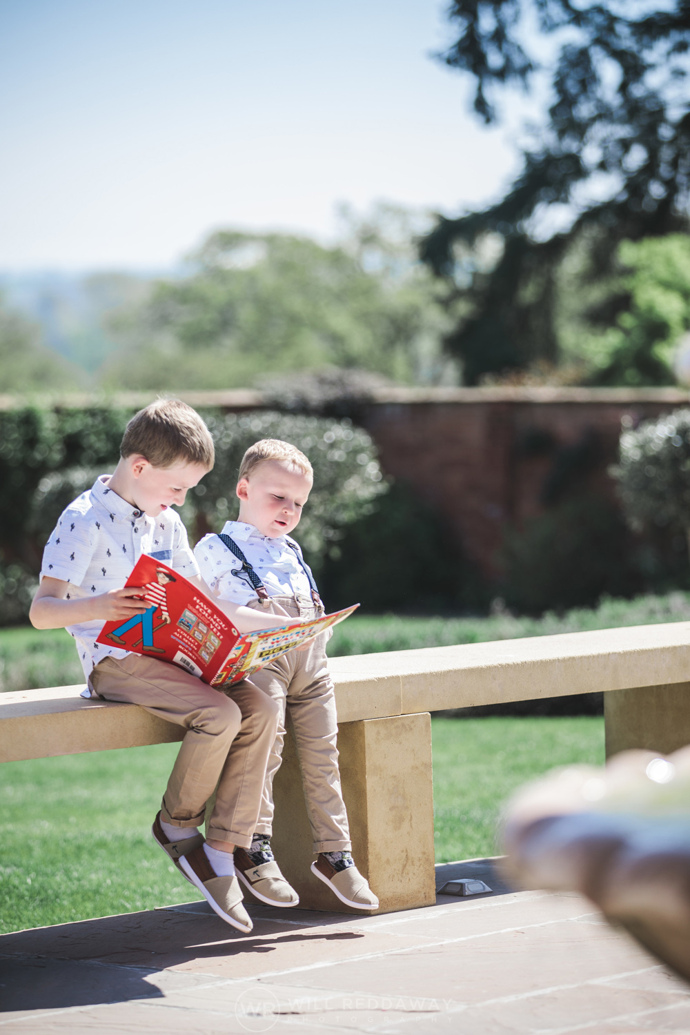 Young boys at wedding sitting and reading in the Walled Garden