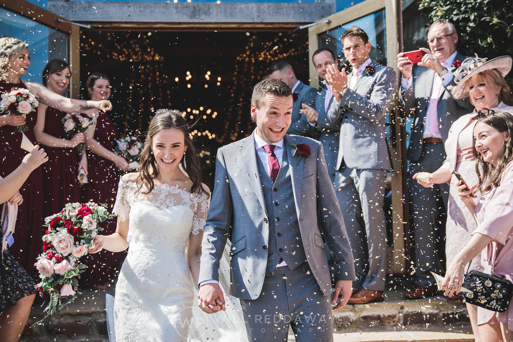 Bride and Groom showered in confetti as the exit The Cider Barn