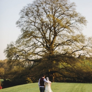 Bride and Goom walk away into the distance towards a large tree