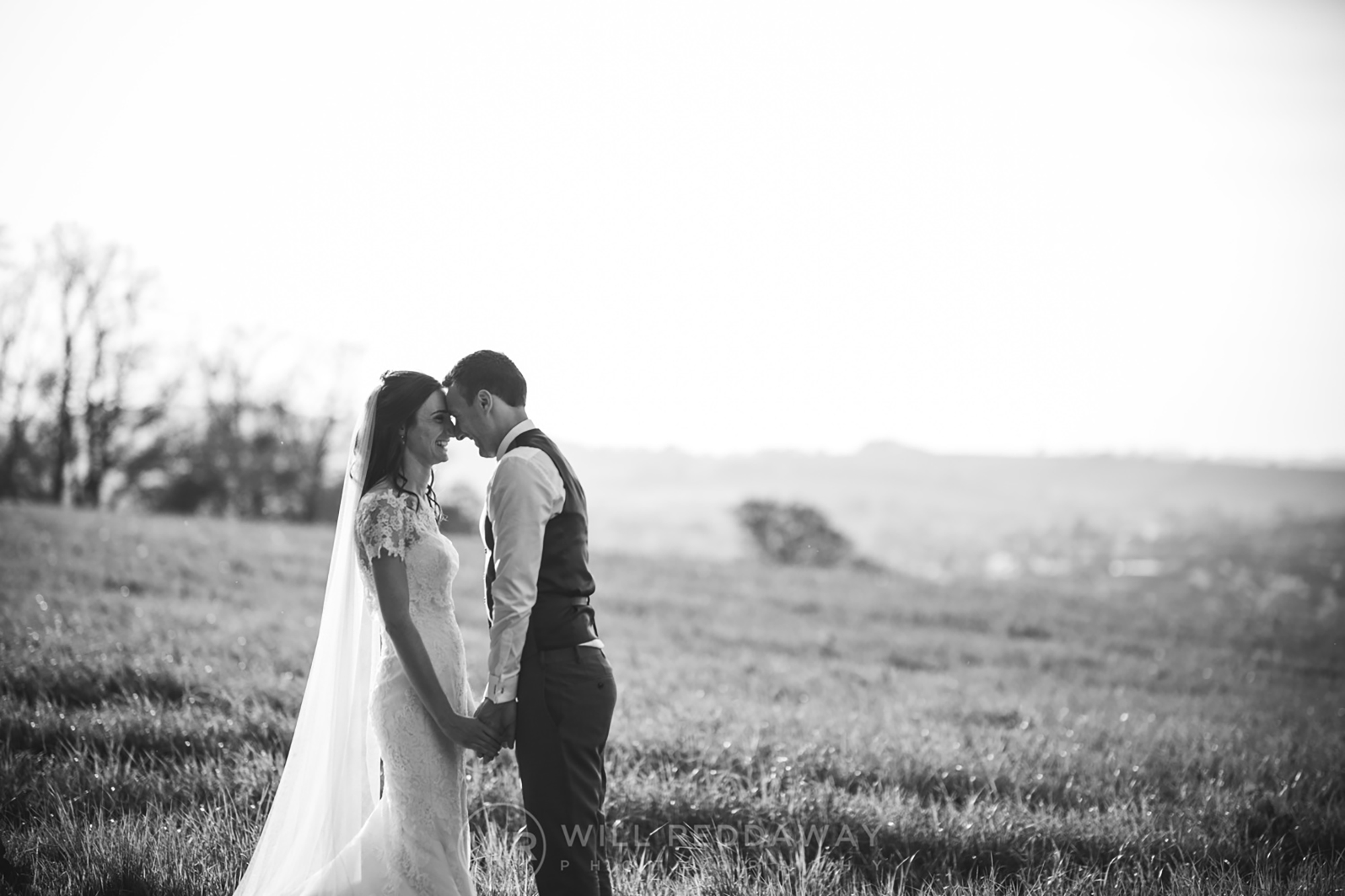 Bride and Groom laugh as they rub noses in a field at Upton Barn