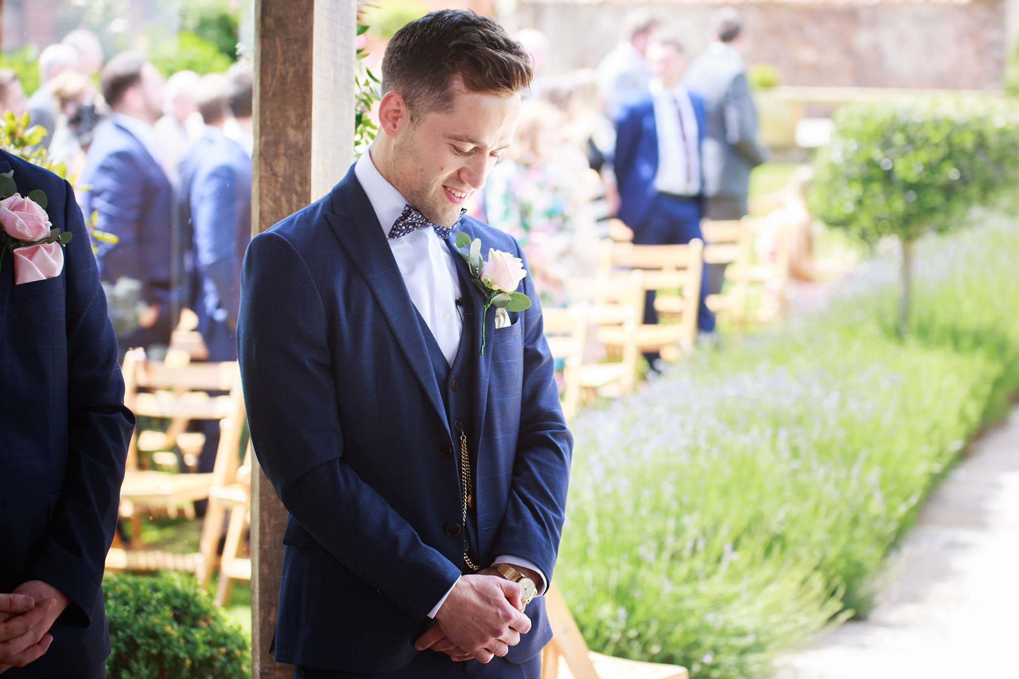 Groom stands awaiting the arrival of his bride in Arbour