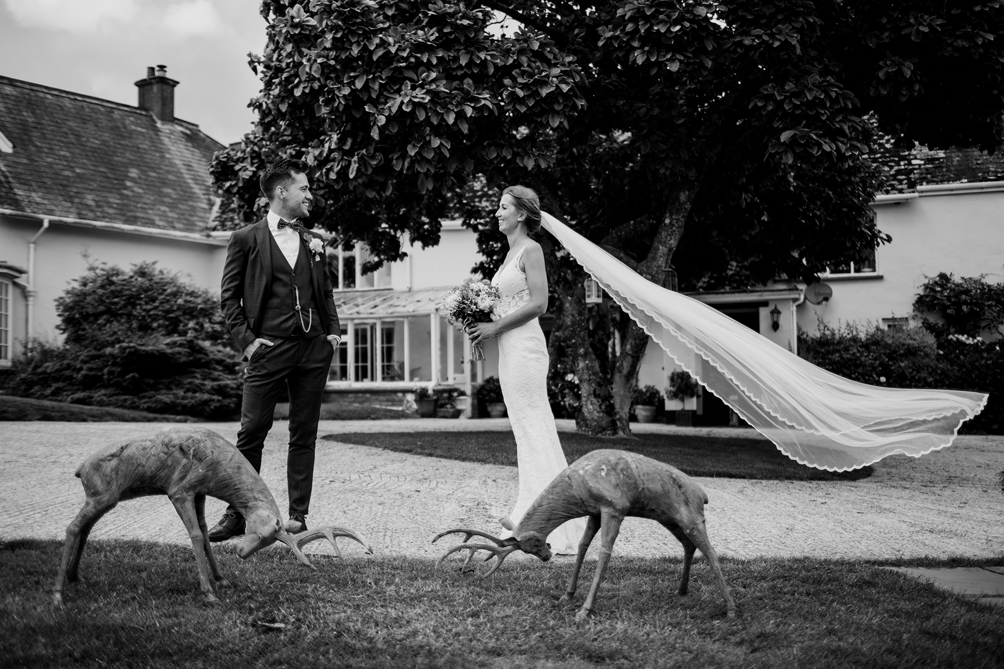 Bride and Groom stand by the large iron deer sulptures