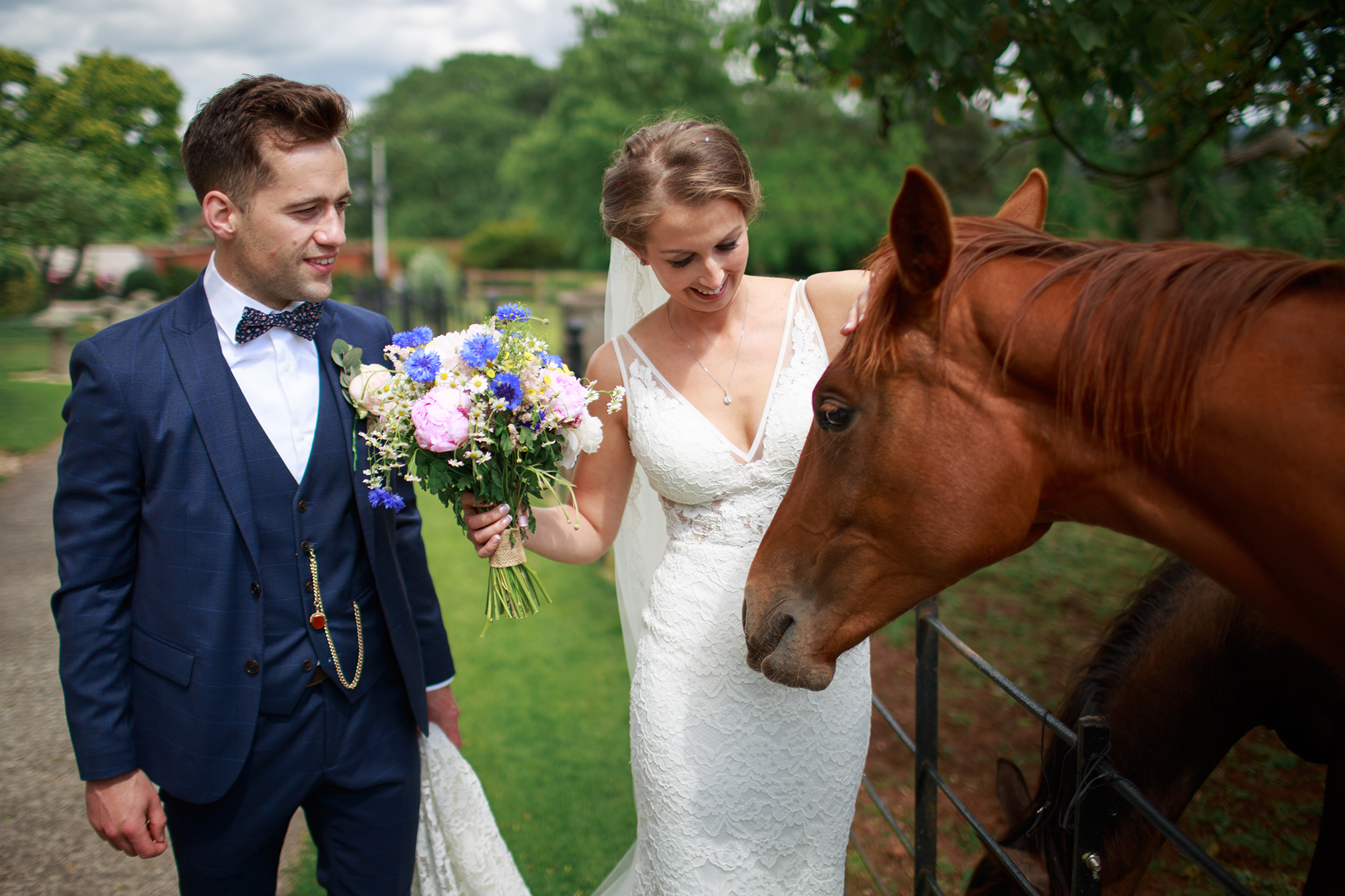 Groom stand by his bride as she strokes one of the horses at the paddaock