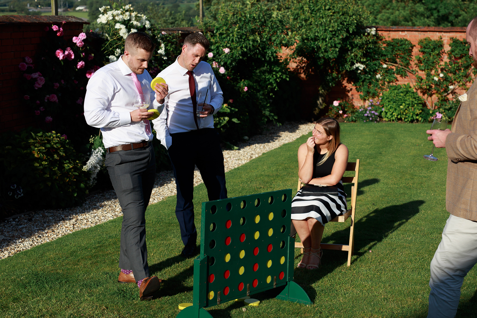 Male guests play giant connect 4 in the Walled Garden