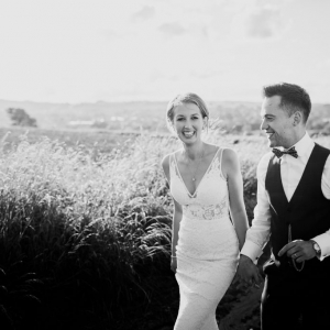 Bride and Groom with beaming smiles walk in a long grass field
