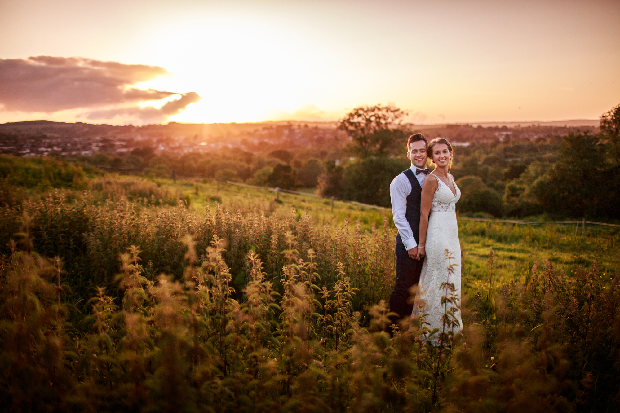 Bride and Groom smile to camera as the sun sets over the Devon fields