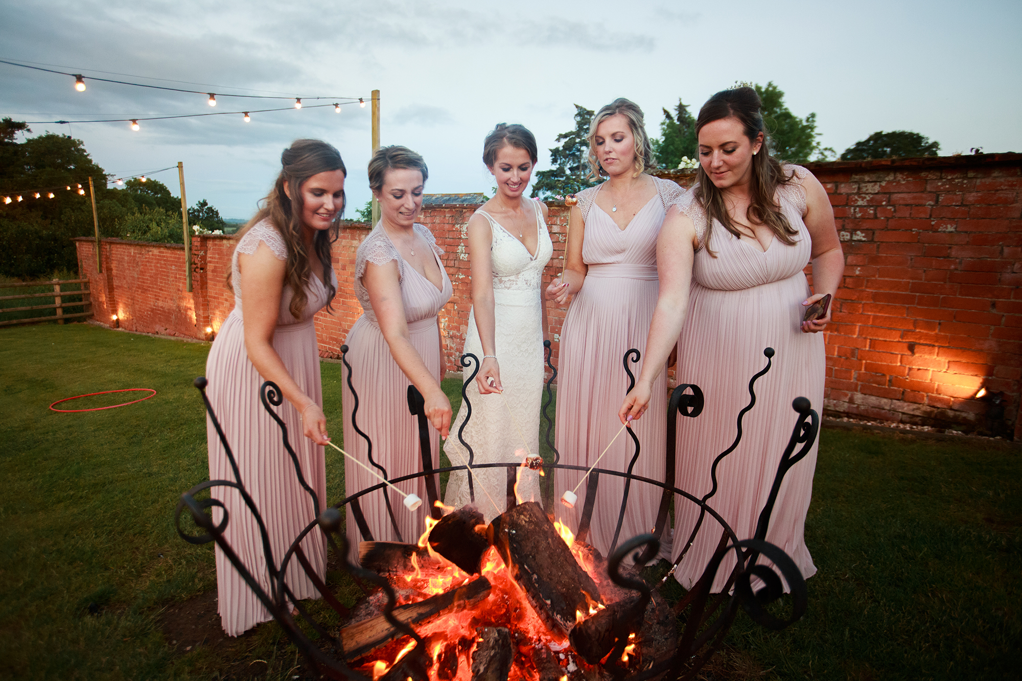 Bride and her maids toast marshmellows over the fire baskets